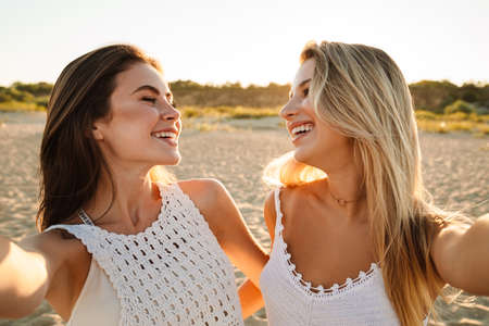 Photo pour Two young caucasian happy women smiling and taking selfie photo while walking on beach - image libre de droit