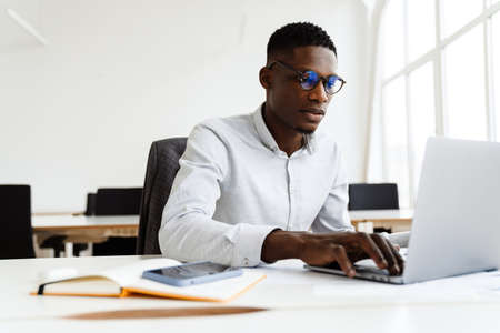 Photo pour Afro american focused man in eyeglasses working with laptop while sitting in office - image libre de droit