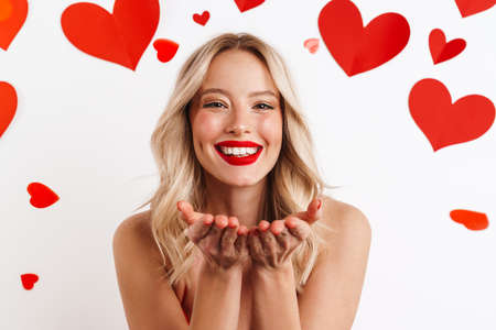 Photo for Cheerful nice girl holding copyspace and smiling isolated over white background with hearts - Royalty Free Image