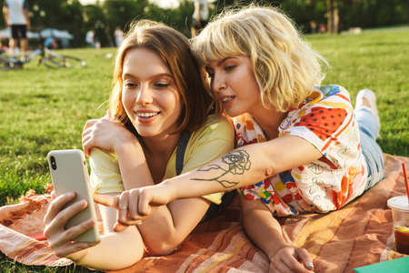 Photo pour Image of pleased nice two women using and pointing finger at cellphone while have picnic on grass in summer park - image libre de droit
