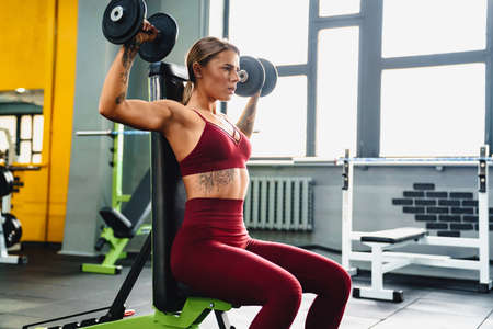 Photo pour Image of strong young woman fitness coach making sport exercise for arms with dumbbells in gym - image libre de droit