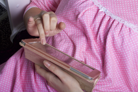 A woman in a nightgown works with a tablet while lying in bed. She touches the screen with her fingers.の写真素材