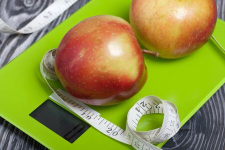 Photo for Apples and a measuring tape lie on the scales. Scales show zero. On brushed pine boards. Symbol of World No Diet Day. - Royalty Free Image