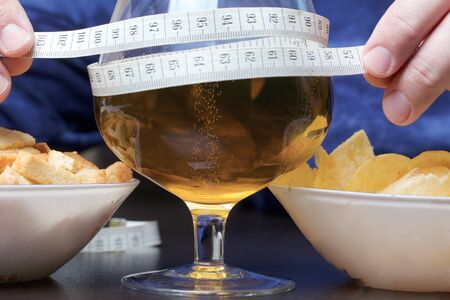 Photo for In front of a man is a glass of beer, wrapped in a measuring tape, which he holds in his hands. Near cups with crackers and chips. World No Diet Day. - Royalty Free Image