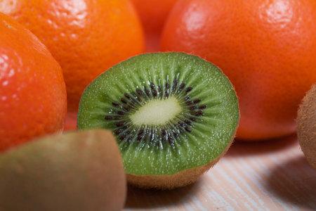 Photo pour Several orange tangerines. Kiwi fruit cut in half. Juicy green flesh is visible. Close-up shot. Lie on a beige surface. - image libre de droit