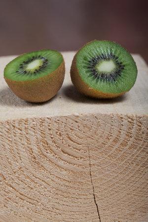 Photo pour Kiwi fruit cut in half. Juicy green flesh is visible. Lies on a wooden block. - image libre de droit