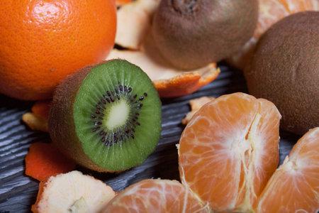 Photo pour Orange tangerines. One without a peel. Kiwi fruit cut in half. Juicy green flesh is visible. Close-up shot. - image libre de droit