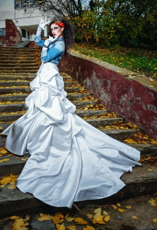 Beautiful bride in magnificent dress stands alone on stairs in autumn day