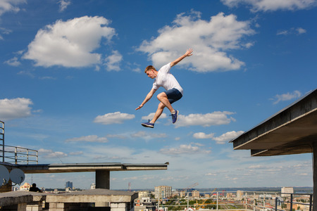 A man is jumping from roof to roof. Parkour. Active lifestyle. Courage. Adrenalin. Roofer
