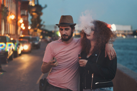 Foto de Loving couple of hipsters on date. Guy in hat and T-shirt is holding electronic cigarette and hugging girlfriend. Girl with curly red hair smokes an ecigarette. They are in streets of evening city. - Imagen libre de derechos