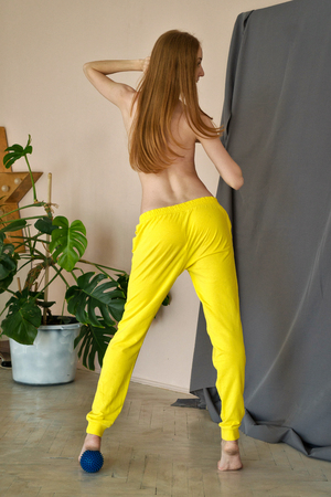 Young slim ballerina in sports pants topless. She trains with massage ball. Girl is barefoot. Grace and sexuality.