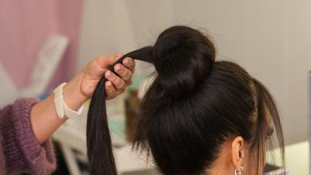 Foto für Professional hairdresser working with client in salon. Earlock hair in hairstylist's hand Master class to create upper bun hairstyle. Tutorial, advanced course. Apprenticeship concept. - Lizenzfreies Bild
