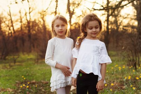 Photo pour Stylish portrait of sisters in spring meadow. Girls posing in white dresses. Family photo - image libre de droit