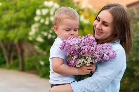 Photo for Young loving mother walking with her little son on spring background. Cute child and her mom on outdoor. Enjoy the good weather and spring flowers. Happiness to be a parent. Time together. - Royalty Free Image