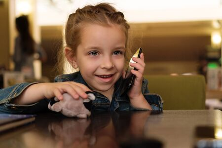 Charming little girl communicates using a mobile phone. Children's tariff. Be in touch. Call relatives