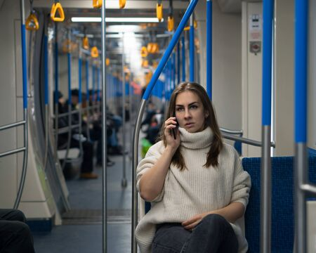 Photo pour Girl speaks on cell phone inside an empty subway train. A beautiful woman tourist of appearance sits in subway car. Portrait of female passenger using mobile phone. - image libre de droit