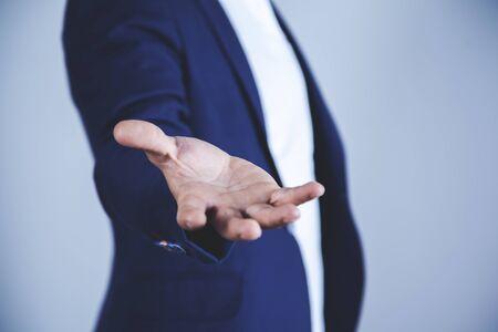 Photo pour young business man empty palm on gray background - image libre de droit