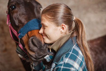 Photo pour Young teenage girl equestrian kissing her chestnut horse. Multicolored outdoors horizontal image. - image libre de droit