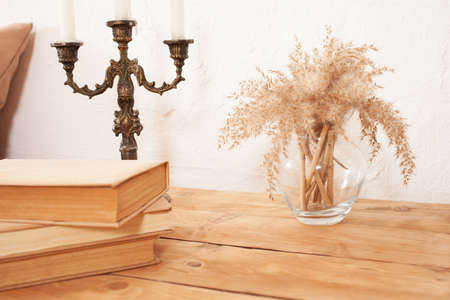 Photo pour Beige interior, brown books, pampas in a glass vase, candlestick. A wooden bedside table. copy space mocup - image libre de droit