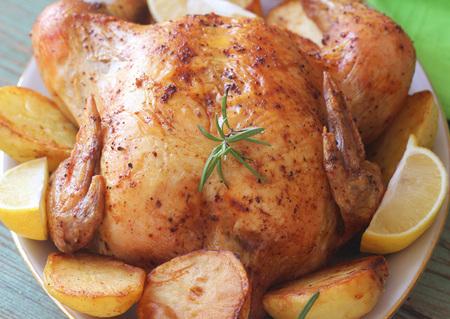 Photo pour Whole roasted chicken with potatoes and lemon - image libre de droit