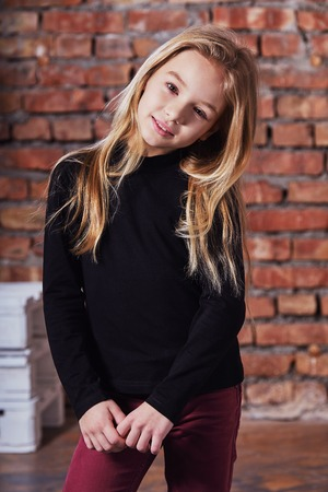 Fashion kid girl. Portrait stylish model child smile. Young cute teenager adorable face. model teen posing against rough brick wall. models tests.