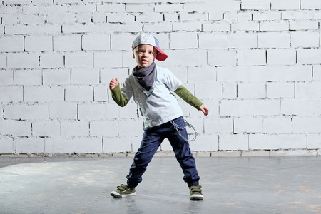 Foto de little child boy model posing in fashionable rapper clothes. studio, brick wall background. Cool young kid dancing break dance.Hip-hop style. - Imagen libre de derechos