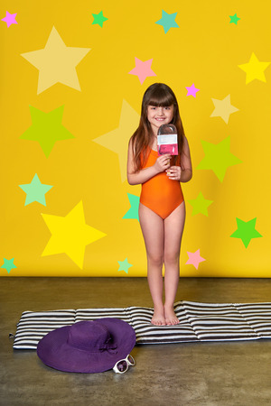 Foto per Fashion summer little girl, bright background,stars,studio. Charming child in swimsuit holding ice cream. - Immagine Royalty Free