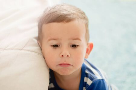 Portrait of 2 year old boy in a white light room in the morning with a sad face expression
