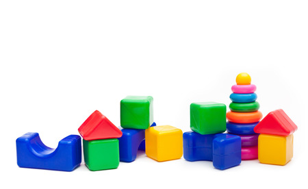 Pyramid build from colored rings and a building blocks isolated on white background