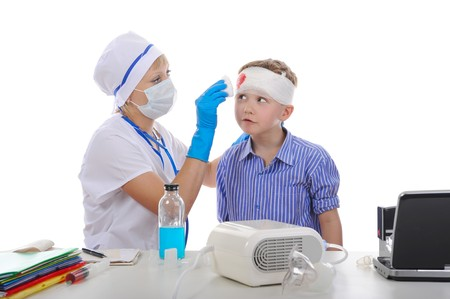 Doctor bandaged the boy's head. Isolated on white background