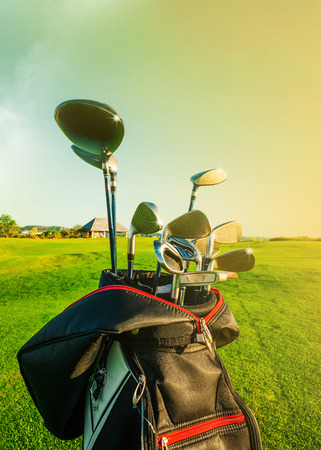 Golf club Bag with golf clubs Green golf field and ball in grass