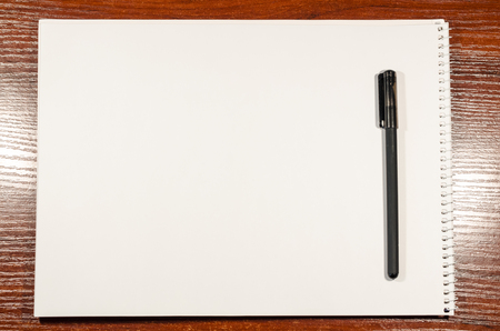 Photo for A blank page of an open notebook is on the wooden table with a black pen. Place for writing anything you want. Business and education concept. Texture background of a white sheet of paper. - Royalty Free Image