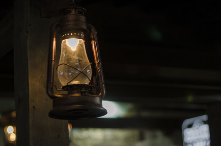 Photo for Old lamp hanging from the ceiling on the dark background. Burning kerosene lamp close up view. Room lighting concept. - Royalty Free Image