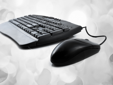 computer keyboard and mouse with lights in the background