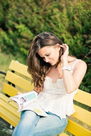 Photo pour Woman read a magazine in park  - image libre de droit