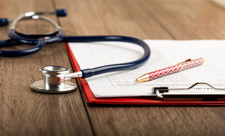 Foto de medical history with stethoscope and pen on wooden desk - Imagen libre de derechos