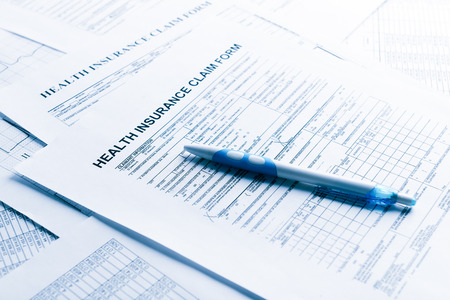 health insurance form, paperwork and questionnaire for insurance concepts. Blue toned