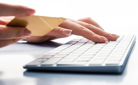 Foto de Hands holding a credit card and using laptop computer for online shopping - Imagen libre de derechos