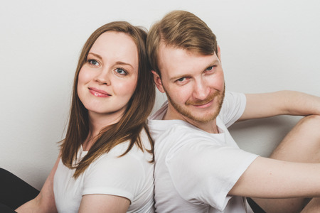 Photo pour Cheerful happy man and woman sitting back to back. - image libre de droit