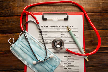 Photo pour Health insurance claim form with stethoscope and surgical mask - image libre de droit