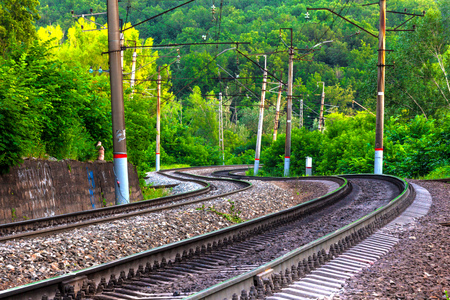 Photo pour Rails and sleepers of a double winding railway track in a green forest between crooked, leaning column posts. - image libre de droit