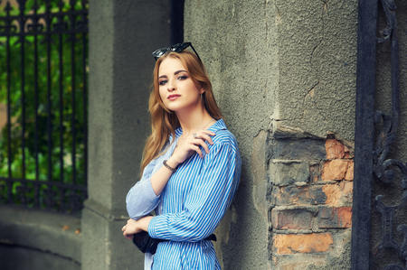 Attractive young girl on the old city street .  Beautiful fashionable woman in summer outdoors . Women's beauty and fashion concept