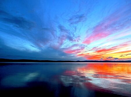 Photo for multi-colored blue and orange sunset sky over the lake, a fantastic picture of clouds, reflections on calm water, the southern Urals, lake Uvildy - Royalty Free Image