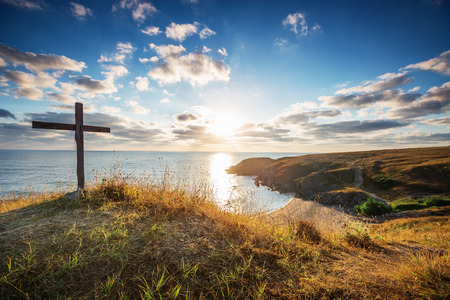 Photo for Christian cross on a wild beach with a wonderful sunrise - Royalty Free Image