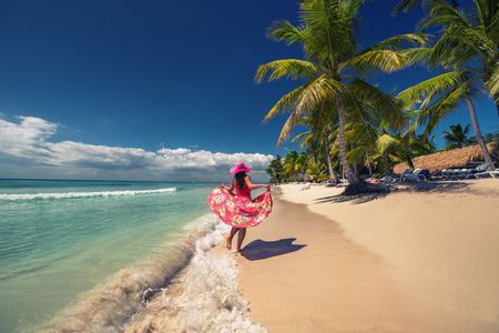 Carefree young woman  walking on the tropical sandy beach, Saona island, Dominican Republic