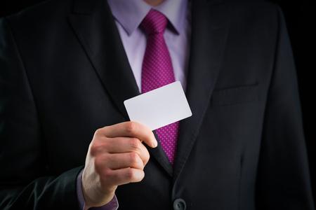 Photo pour Businessman in elegant suit and with a tie, shows business card with copy space, studio shot - image libre de droit
