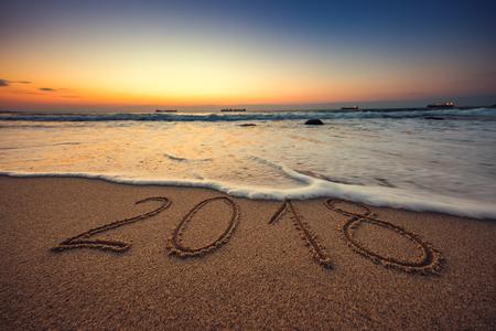 Photo pour Happy New Year 2018 concept, lettering on the beach. Sea sunrise. - image libre de droit