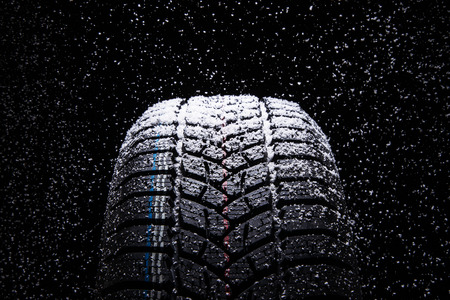 Photo pour Winter Car tires with snow on black background - image libre de droit