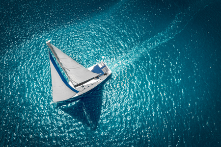Foto de Regatta sailing ship yachts with white sails at opened sea. Aerial view of sailboat in windy condition. - Imagen libre de derechos