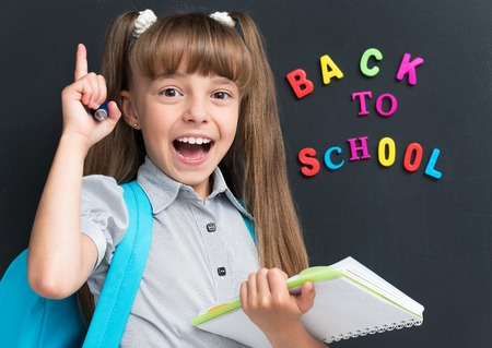 Back to school concept. Happy schoolgirl with backpack and notebook at the black chalkboard in classroom.